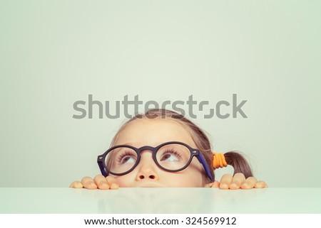 cute little girl hiding behind the table Stock photo ©