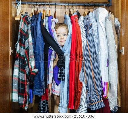 Cute little girl hiding inside wardrobe from her parents early morning
