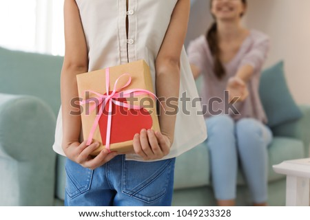 Cute little girl hiding present for mother behind her back ストックフォト ©