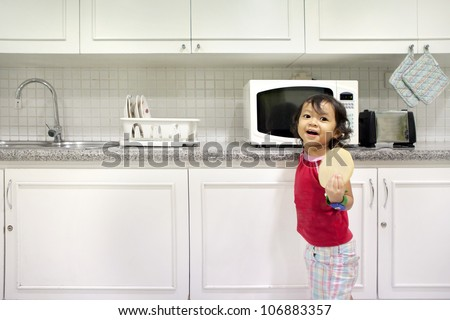 Cute little girl holding a bread in kitchen. shot in the kitchen with modern interior