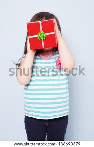cute little girl holding a red gift box in front of her face