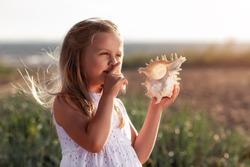 Cute little girl holding a seashell at the beach