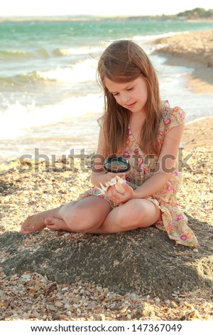 cute little girl holding a seashell/Young girl in a summer dress sitting on the beach and dreams