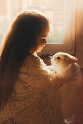 Cute little girl holding a white rabbit in her arms. Long hair, rustic comfort, postcard, friendship with animals, rest at nature, countryside life.