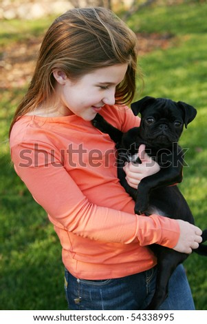 cute little girl holding black pug puppy