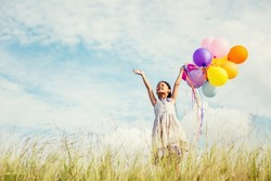 Cute little girl holding colorful balloons in the meadow against blue sky and clouds,spreading hands.