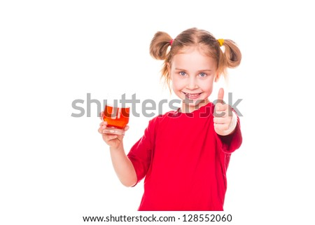 Cute little girl holding glass with juice smiling isolated on white