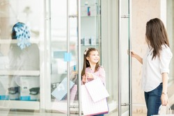 Cute little girl holding lots of shopping bags entering a store with her mother opening the door in a shopping mall