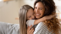 Cute little girl hug cuddle excited young mum show love and affection, smiling mother and funny small preschooler daughter have fun at home embrace sharing close tender moment together