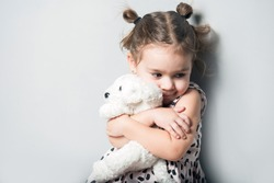 Cute little girl huggin toy puppy on grey background
