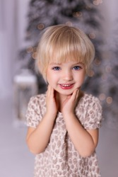 Cute little girl in a beautiful dress. Beautiful  girl posing near the christmas tree. Merry Christmas and Happy New Year. Christmas celebration.
