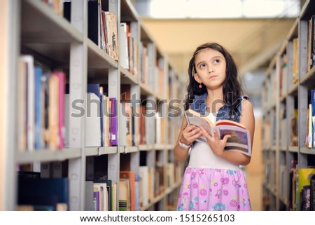 Cute little girl in a library holds a book in her hands while looking at the horizon imagining. Children creativity, learning and imagination. #1515265103
