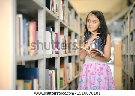 Cute little girl in a library holds in her hands the book she is reading and smiles while imagining the stories ..Children creativity, learning and imagination. #1510078181