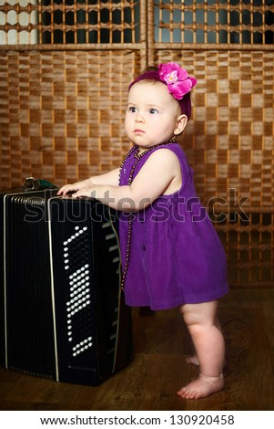 cute little girl in a purple dress with accordion