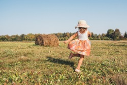 Cute little girl in a straw hat and summer dress fun dancing on the field with a big stack of hay. Summer in the village.