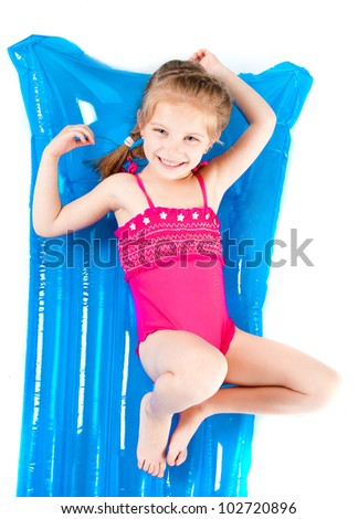 cute little girl in a swimming suit on an inflatable mattress