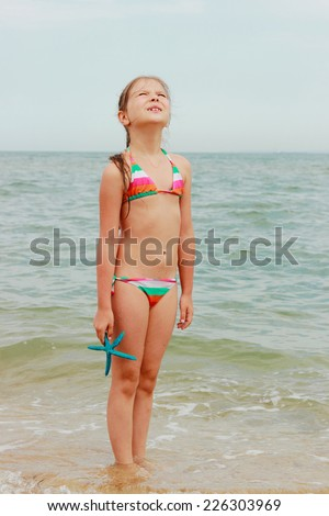 Cute little girl in a swimsuit holding a blue starfish and walks on the water on the beach