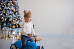 Cute little girl in a white sweater sits on a toy antique blue car and smiles. Christmas tree in the background, gifts, lights.