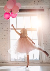 Cute little girl in beautiful dress is dancing at light sunny room with pink air balloons in hand.