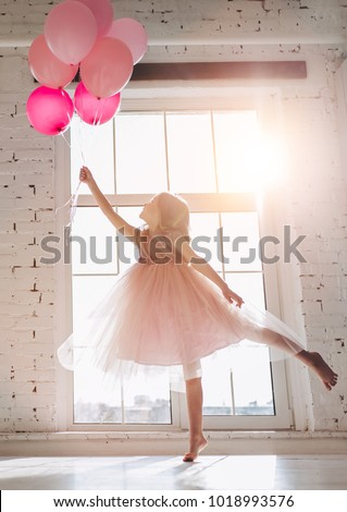 Cute little girl in beautiful dress is dancing at light sunny room with pink air balloons in hand. #1018993576