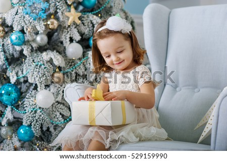 cute little girl in bklom dress sitting in a chair and opens a box with a present for background Christmas tree with blue ornaments. Xmas holiday concept