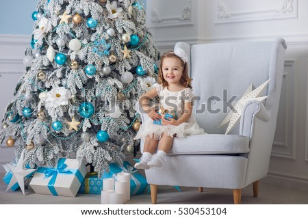 cute little girl in bklom dress sitting in a chair and opens box with present for background Christmas tree blue ornaments