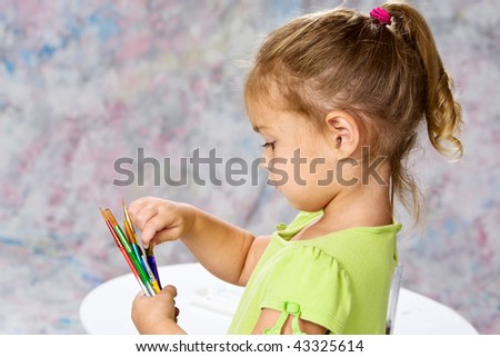 Cute little girl in green blouse playing with water colors on easel.