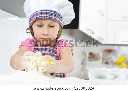 Cute little girl in hat and apron cooking cookies