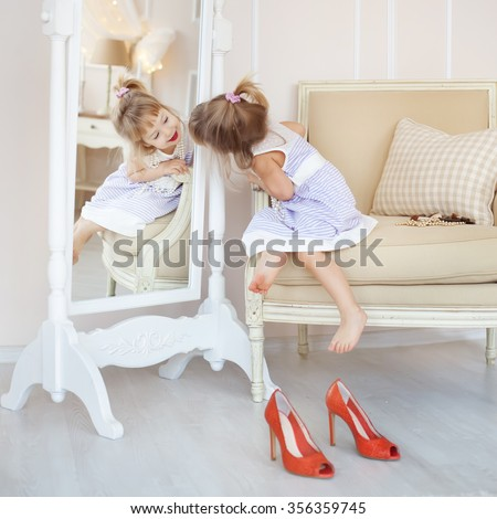 Cute little girl in her mother's room, using makeup to imitate adults Сток-фото ©