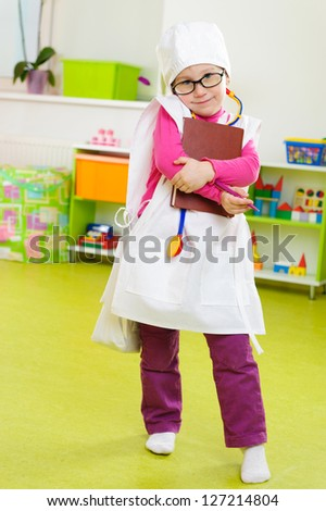 Cute little girl in medical uniform playing in doctor