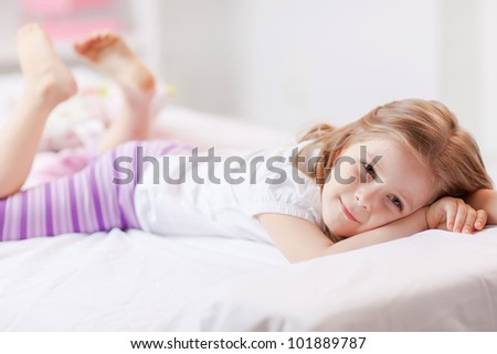 Cute little girl in pajamas on the bed
