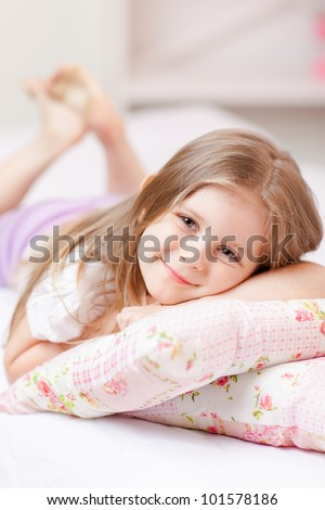 Cute little girl in pajamas on the bed in the morning
