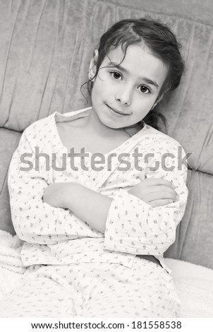 cute little girl in pajamas sitting on the couch ( black and white )