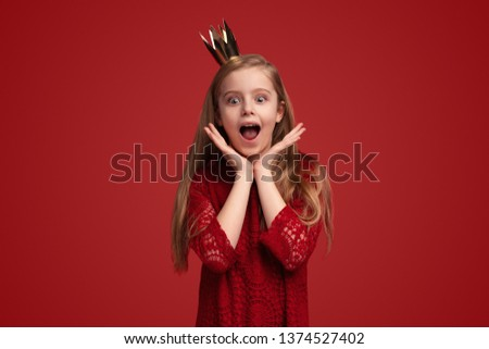 Cute little girl in princess crown keeping hands near face and shouting in amazement while standing against red background