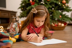 Cute little girl in red dress writes letter to Santa Claus next to Christmas tree at home