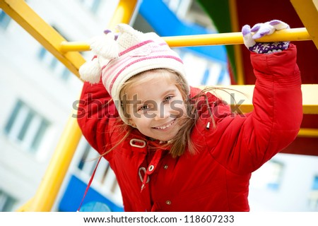 Cute little girl in red on outdoor playground equipment