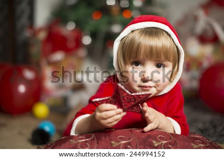Cute little girl in santa costume , christmas background with a red ornament