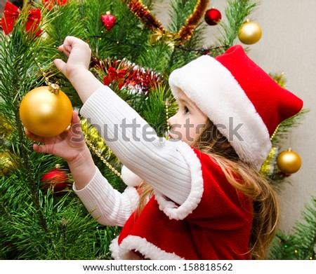 Cute little girl in santa hat decorating the christmas tree