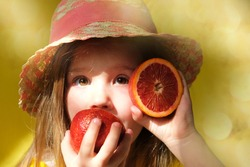 Cute little girl in straw hat licking orange fruit.  gift tour for all family. Happy weekend. Health diet.
