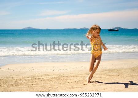 Cute little girl in swimsuit dancing near the sea. #655232971