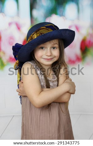 Cute little girl in too big hat smiles cringed with crossed arms