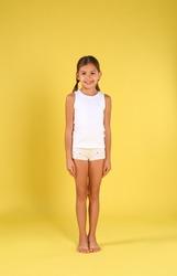Cute little girl in underwear on yellow background