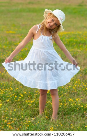 Cute little girl in white dress and hat walking on the meadow on sunny summer day.