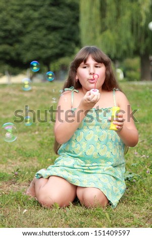 Cute little girl is blowing a soap bubble/Cheerful smiling little girl walks in the park and blows bubbles outside