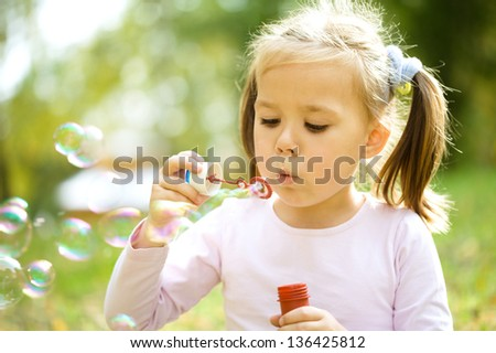 Cute little girl is blowing a soap bubbles