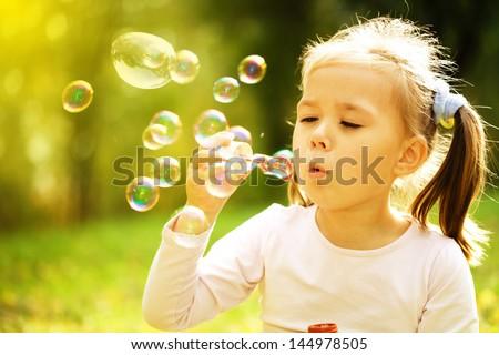 Cute little girl is blowing a soap bubbles Stock foto ©