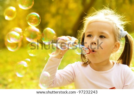 Cute little girl is blowing a soap bubbles - stock photo
