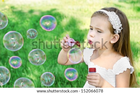 Cute little girl is blowing a soap bubbles in summer day