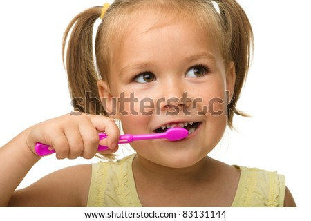 Cute little girl is cleaning teeth using toothbrush, isolated over white