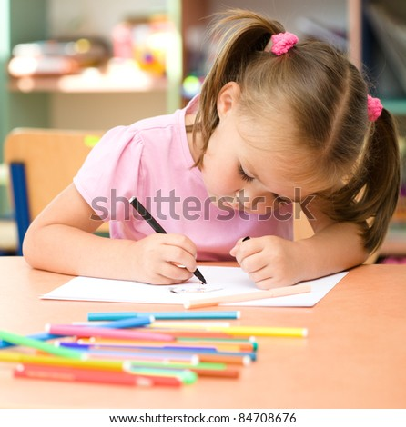 Cute little girl is drawing with felt-tip pen in preschool